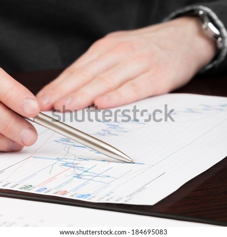 Business men reading contract with pen in hand - 1 to 1 ratio - stock photo