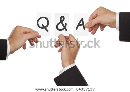 Business men's hand holding cards forming Q&A - stock photo