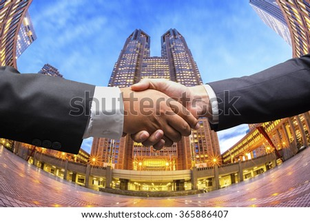 Business men shaking hands on business background - stock photo