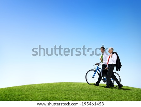 Business Men Walking Through the Field with a Bicycle - stock photo