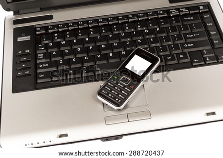 Business mobile cellphone resting on laptop computer - stock photo