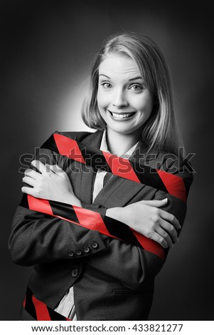 Business model is tied up with a black and red stripe tape wound around her.  - stock photo