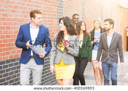 Business multiracial group walking in London. They all are young, smiling and wearing smart casual clothes. Mixed race group. Teamwork and business concepts. - stock photo