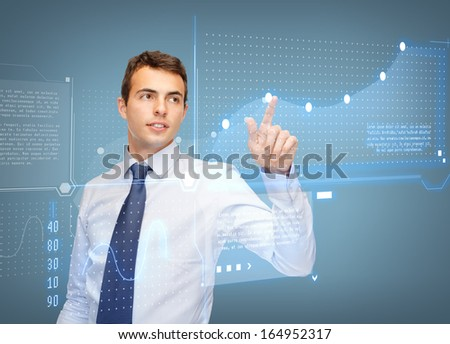 business, new technology and communication concept - businessman working with virtual screen and graphs on it - stock photo