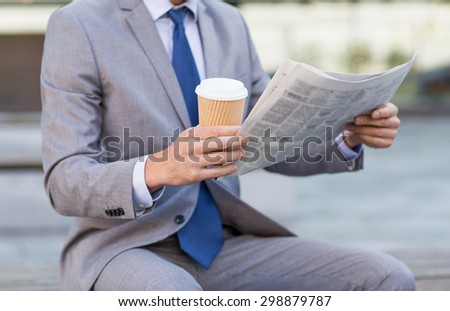 business, news, break and people and concept - close up of businessman reading newspaper and drinking coffee from paper cup over office building - stock photo
