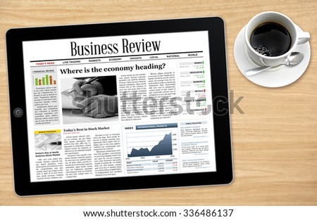 Business News on Tablet with a Cup of Coffee. - stock photo