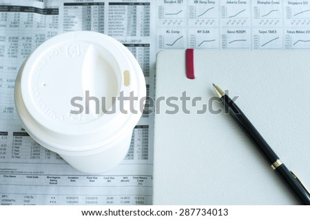 Business newspaper with cup of coffee in the morning - stock photo