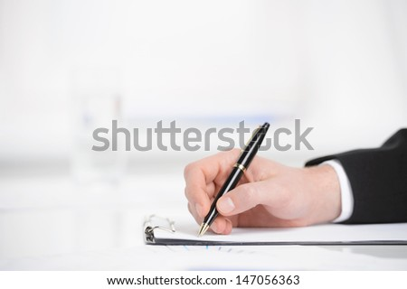 Business notes. Close-up of hand writing something in a note pad - stock photo