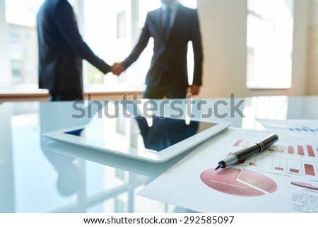 Business objects at workplace with handshaking partners on background - stock photo