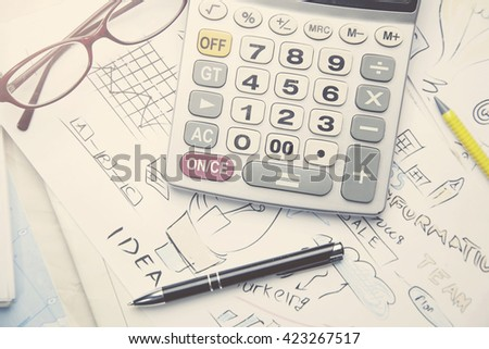 business objects - graphs, charts, pen and calculator on the table - stock photo