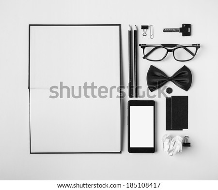 Business objects in order on white desk. /Overhead of essentials office objects in black and white. - stock photo