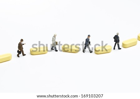 Business of healthcare. Business figurines placed with pills. - stock photo