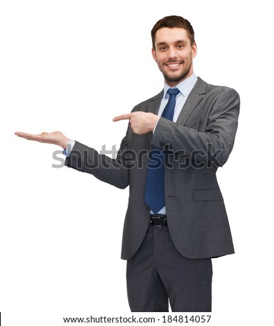 business, office, advertising and people concept - friendly young buisnessman pointing finger to something on the palm of his hand - stock photo