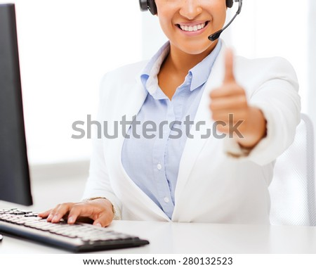 business, office and communication concept - african female helpline operator with headphones showing thumbs up - stock photo