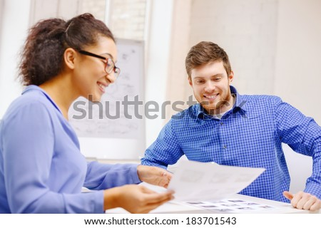 business, office and startup concep - smiling creative team with papers working in office - stock photo