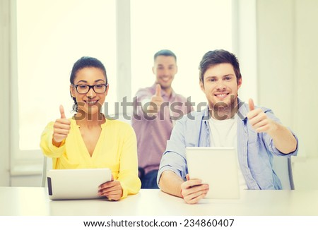business, office and startup concept - creative smiling team with tablet pc computers at office showing thumbs up - stock photo