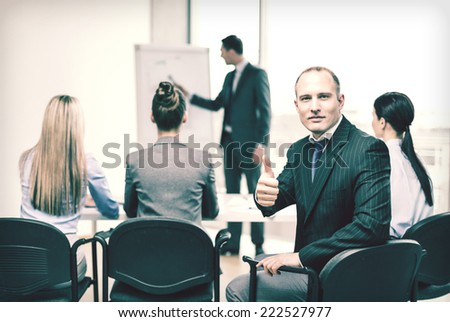 business, office and success concept - confident businessman with team in office showing thumbs up - stock photo