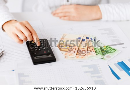 business, office, household, school, tax and education concept - woman hand with calculator and euro money - stock photo