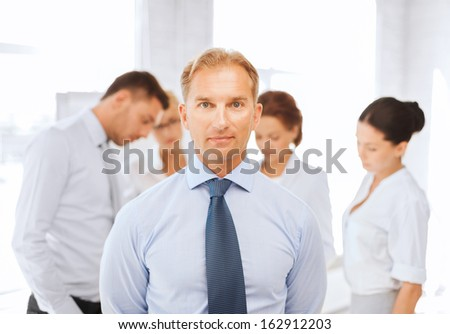 business, office, school and education concept - smiling handsome businessman with team on the back - stock photo