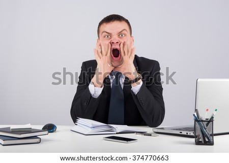 Business,office, technology, finances and internet concept - Angry businessman sitting at the table and screaming over gray background - stock photo