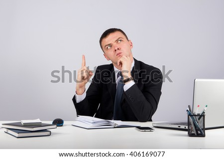 Business,office, technology, finances and internet concept - business man at office holding finger up: idea or warning  on gray background - stock photo