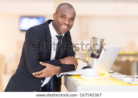 Business on the go. Cheerful young African man in formalwear using his laptop while leaning at bar  - stock photo
