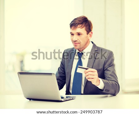 business, online banking, internet shopping concept - smiling man with laptop and credit card in office - stock photo