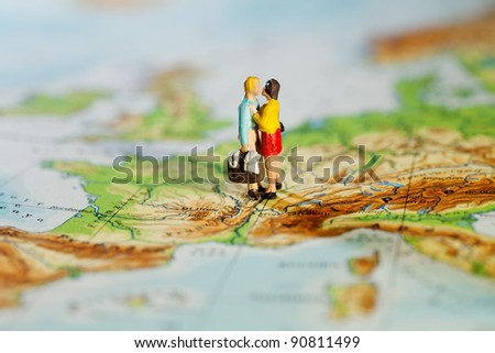 Business Or Personal Travel Concept. Two miniature figurines of a man carrying luggage and his wife embracing while standing on a map of Europe. - stock photo