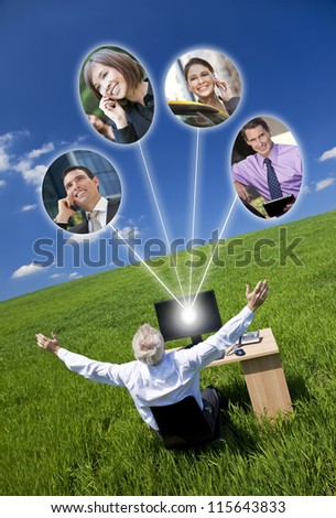 Business or social network connections concept photograph of man businessman sitting at a desk using a computer in a green field raising her arms into a bright blue sky - stock photo