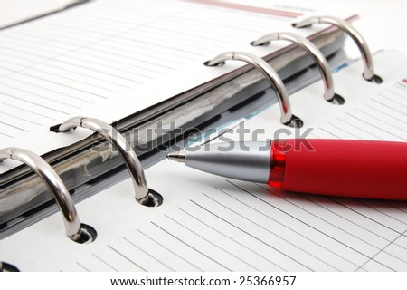 business organizer on white background with pen - stock photo