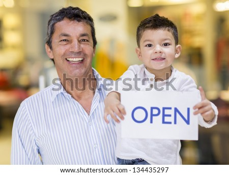 Business owner and son holding an open sign - stock photo