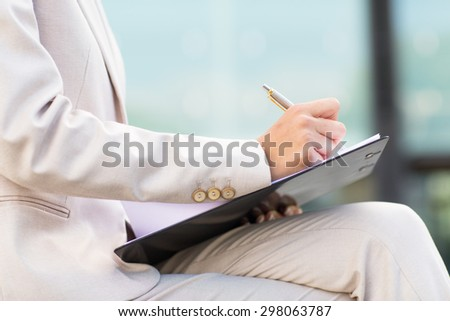 business, paperwork and people and concept - close up of business woman writing or signing paper on clipboard - stock photo