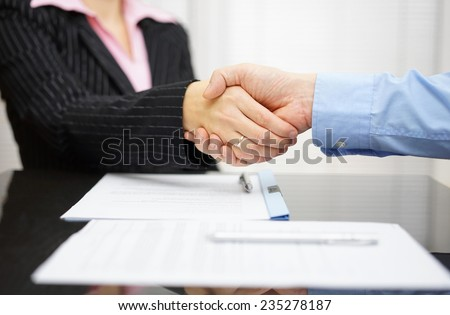 business partner and client  are handshaking over signed contract - stock photo