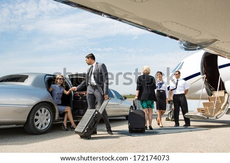 Business partners about to board private jet while airhostess and pilot greeting them - stock photo