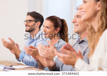 Business partners applauding at the meeting sitting in a row. Successful businesspeople applauding after presentation. Happy group of business team clapping hands in boardroom. - stock photo