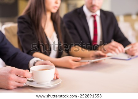 Business partners are meeting in restaurant to discuss plan of work. Close-up of hands with tablet and a cup of tea. - stock photo