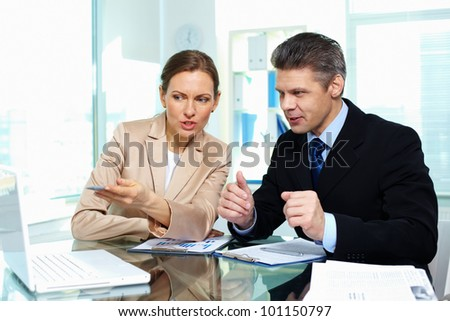 Business partners discussing possible options in terms of a new strategy - stock photo