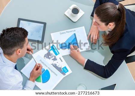 Business partners discussing work together.Top view of young man and woman analyzing documents and statistics at table. - stock photo