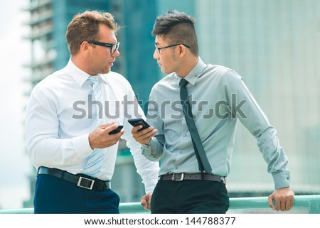 Business partners exchanging contacts outdoors in the city - stock photo