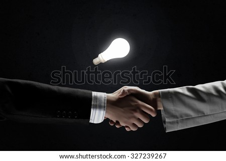 Business partners handshake and glowing light bulb - stock photo