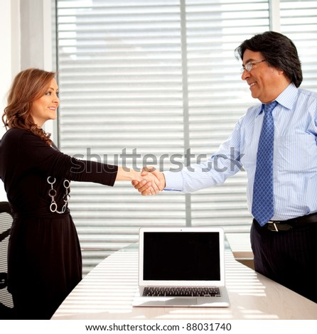 Business partners handshaking at the office sealing a deal - stock photo