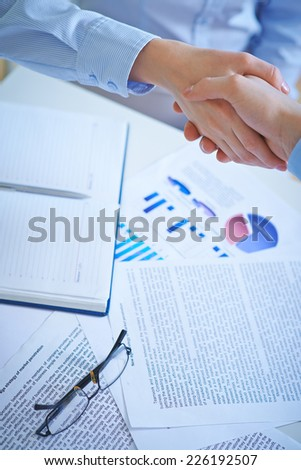 Business partners handshaking over workplace with business documents - stock photo
