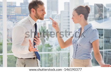Business partners having a heated argument by large windows - stock photo