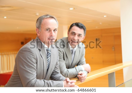 Business partners meeting in lobby - stock photo