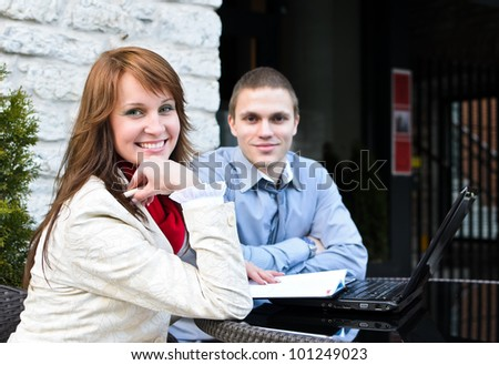 Business partners meeting: Male and female sitting outdoors. Focus on female. - stock photo