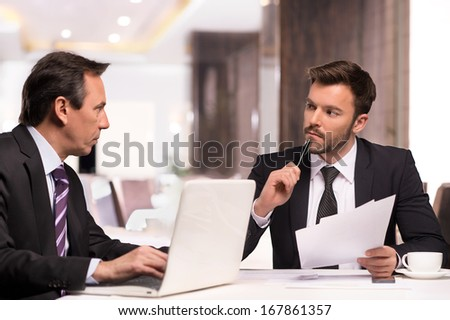 Business partners meeting. Two confident business people in formalwear discussing something while sitting at the restaurant - stock photo