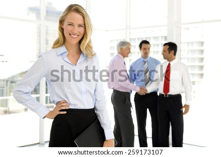 Business Partners shaking hands in the background and beautiful businesswoman looking at camera on foreground - stock photo