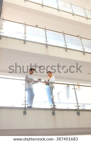 Business partners talking in corridor of multi-storey building. - stock photo