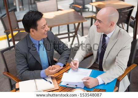 Business partners talking while one of them signing a contract viewed below - stock photo