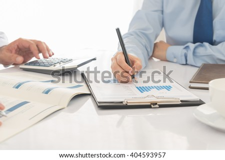 Business partners together to discuss the business plan at the meeting and analyze financial numbers to view the performance of the company. - stock photo